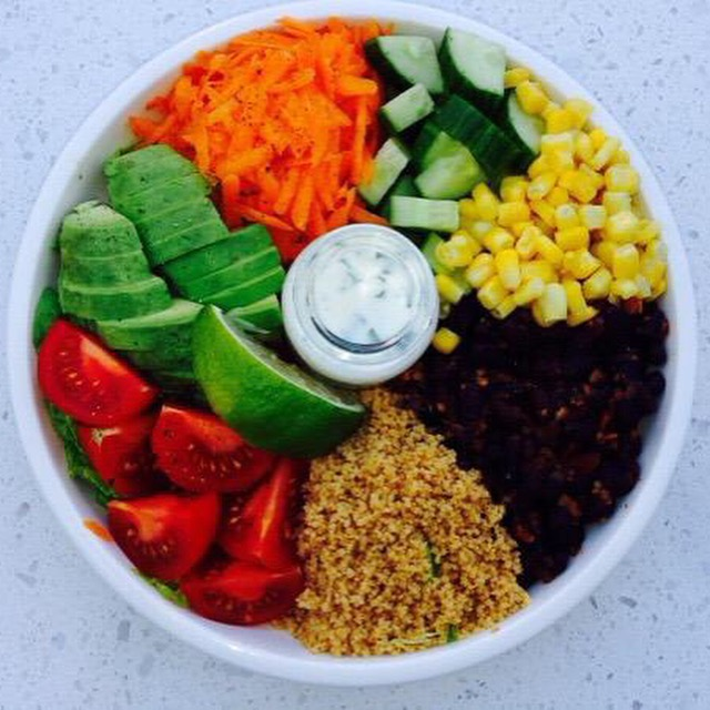 Large salad with carrots, cucumbers, corn, avocado, tomatoes, black beans and coucous with a dressing in the middle