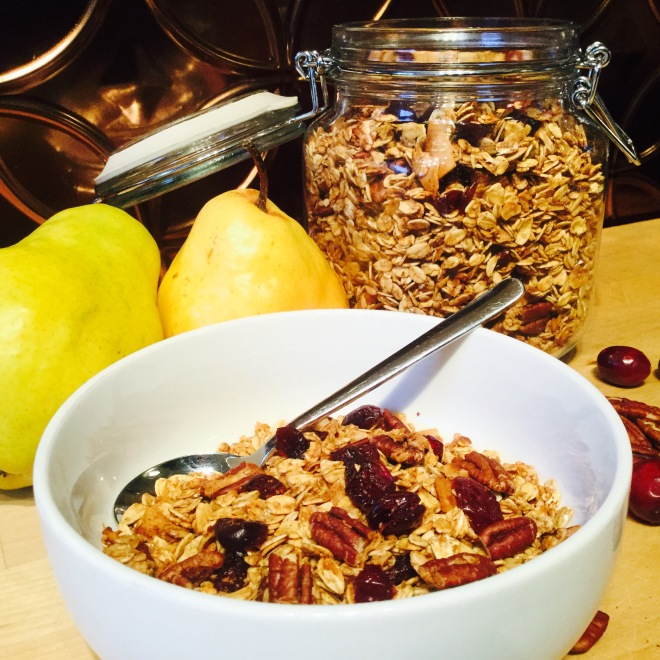 Bowl of granola with pears, pecans and cranberries, large container of granola in background