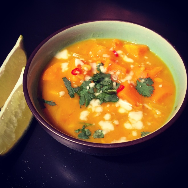 A bowl of Thai Sweet Potato and Lentil Curry with 2 wedges of fresh lime